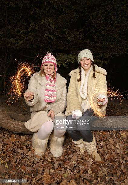 Two teenage girls (13-14) sitting on log, playing with sparklers