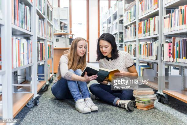 two teenage girls sitting on the floor in a public library reading in a book - literatura - fotografias e filmes do acervo