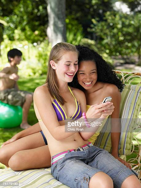 Two teenage girls sitting outdoors in summer with cell phone smiling