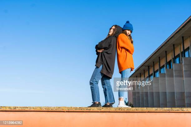 two teenage girls standing back to back on a wall against blue sky - seulement des adolescents ou adolescentes photos et images de collection