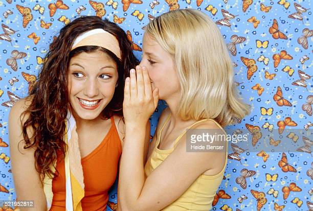 Two teenage girls standing in front of wallpaper with butterflies