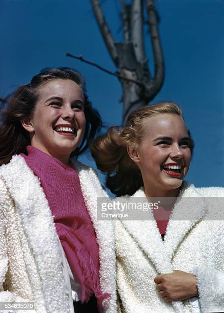 Two teenage girls standing outside wearing white furry coats Los Angeles California 1950