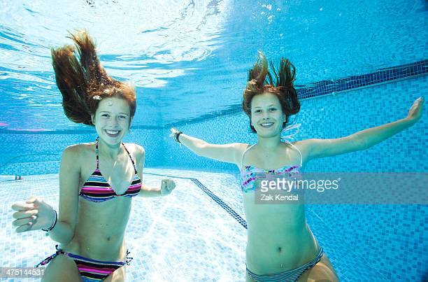 Two teenage girls swimming underwater in swimming pool