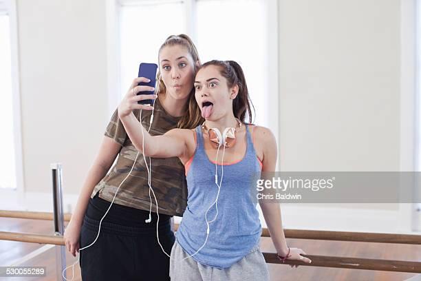 Two teenage girls taking smartphone selfie in ballet school