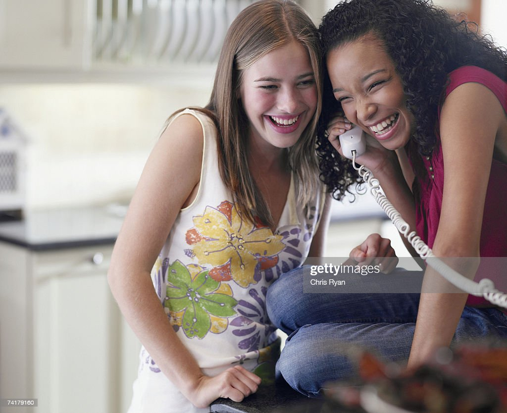 Zwei weibliche Teenager reden am Telefon lacht : Stock-Foto