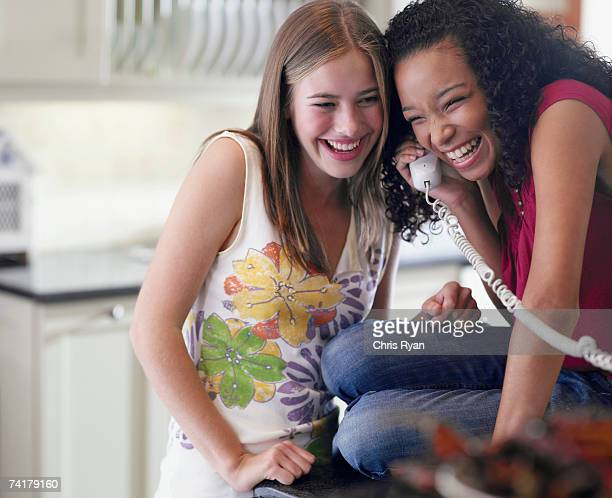 Two teenage girls talking on telephone laughing