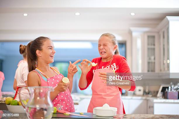 Two teenage girls tasting sour lemons in kitchen
