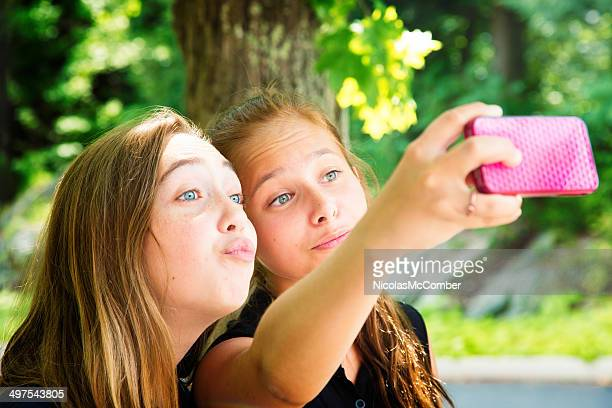 Two teenage girls use phone for silly Summer Selfie