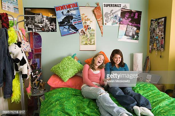 Two teenage girls (14-16) using laptop on bed, laughing