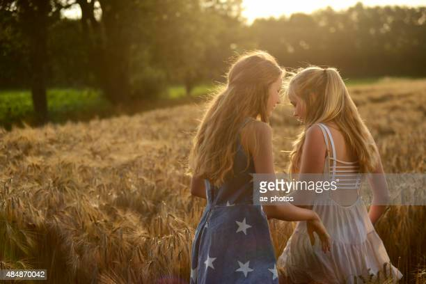 Two teenage girls walking in a barley field
