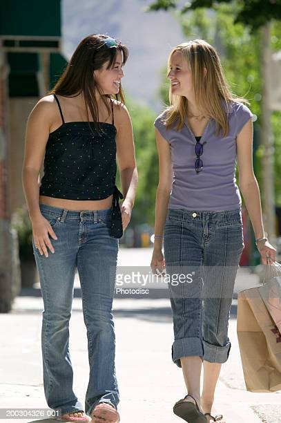two teenage girls (16-17), walking on sidewalk - girl wear jeans and flip flops stock photos and pictures