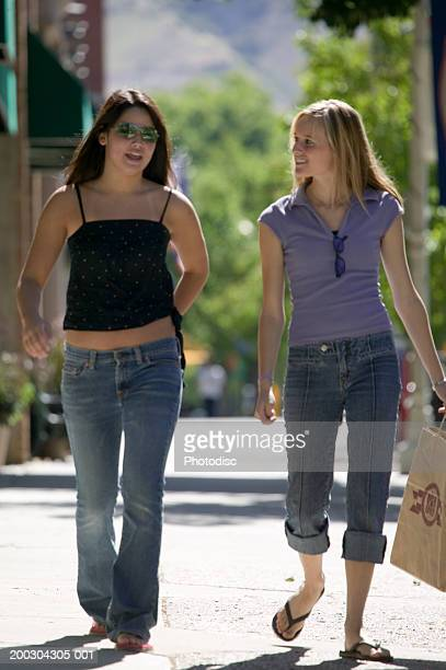 two teenage girls (16-17), walking side by side on sidewalk - girl wear jeans and flip flops stock photos and pictures