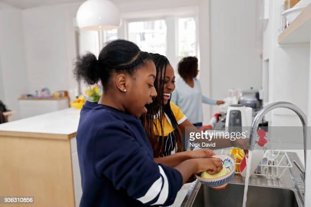 two teenage girls (12-13, 14-15) washing dishes - incidental people stock pictures, royalty-free photos & images