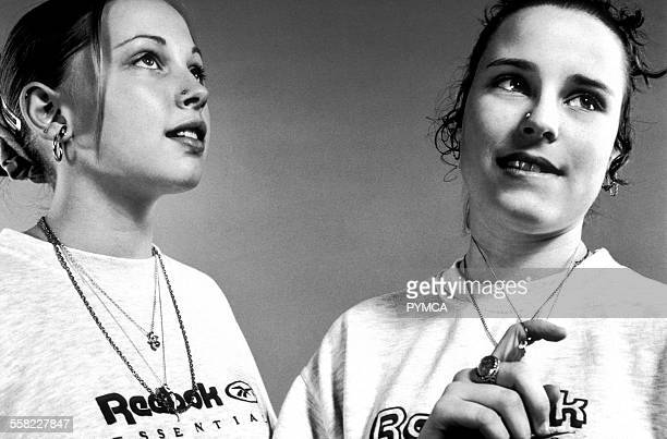 Two teenage girls wear jewellery and Reebok tshirts UK 1990s