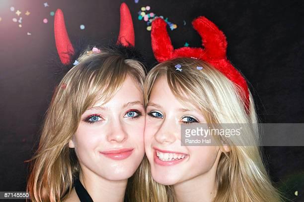 Two Teenage girls wearing devils' horns smiling