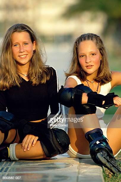 Two teenage girls wearing inline skating gear, portrait