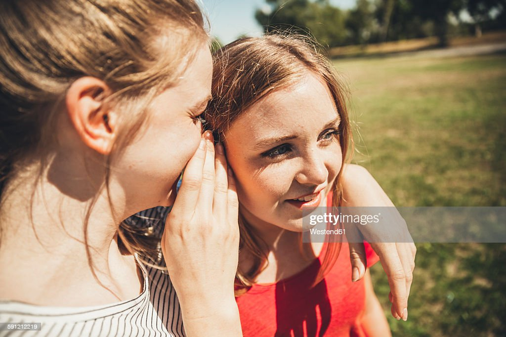 Two teenage girls whispering in park : Stock Photo