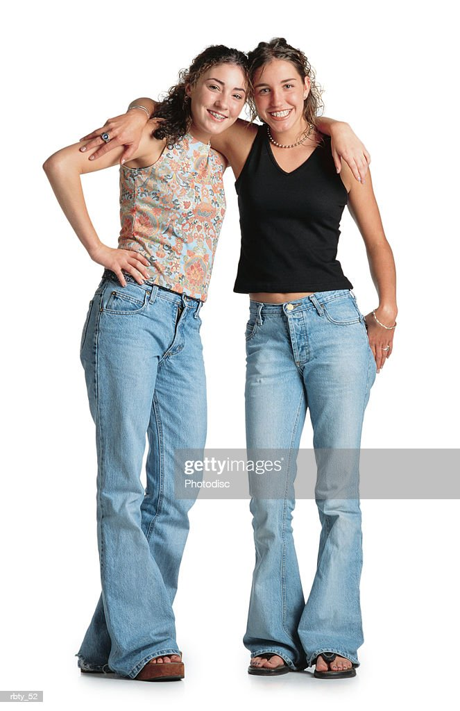 two teenage girls with curly brown hair stand with their arms around each others shoulders wearing tank tops and blue jeans they smile at the camera : Foto de stock