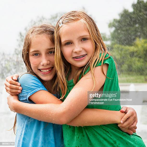 """two teenage girls with their arms around eachother - """"compassionate eye"""" stockfoto's en -beelden"""