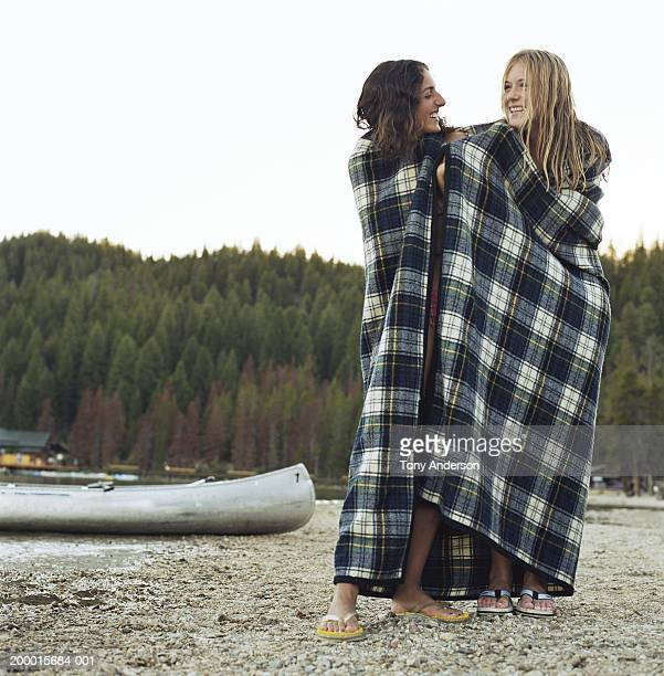 Two teenage girls (16-18)wrapped in blanket near lake