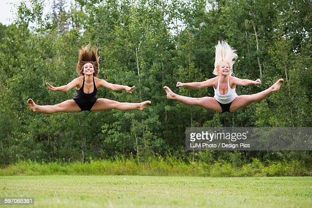 Two teenage gymnasts practicing their routines outdoors in a park, doing split jumps