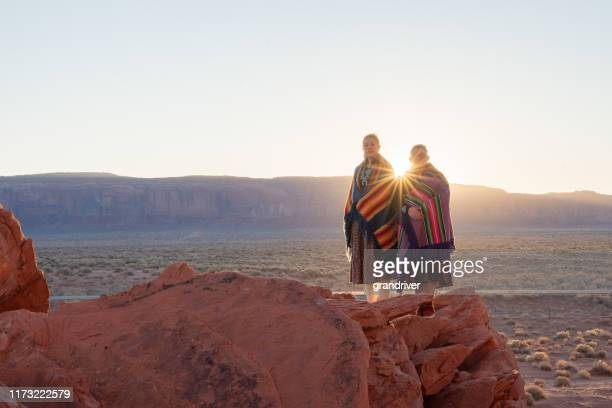 two teenage native american indian navajo sister in traditional clothing enjoying the vast desert and red rock landscape in the famous navajo tribal park in monument valley arizona at dawn - cherokee indian women stock pictures, royalty-free photos & images