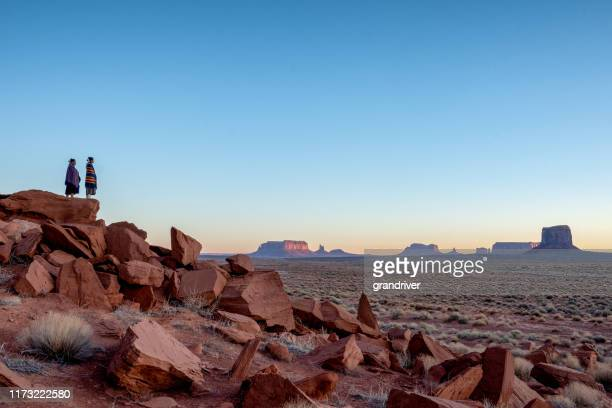 two teenage native american indian navajo sister in traditional clothing enjoying the vast desert and red rock landscape in the famous navajo tribal park in monument valley arizona at dawn - cherokee culture stock pictures, royalty-free photos & images