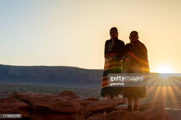 夜明けにアリゾナ州モニュメントバレーの有名なナバホ部族公園で広大な砂漠と赤い岩の風景を楽しむ伝統的な衣服の2つのティーンエイジネイティブネイティブインディアンナバホ姉妹 - ネイティブアメリカン ストックフォトと画像