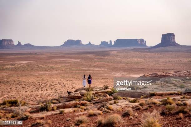 deux adolescentes navajo amérindiens regardant au-dessus du vaste désert dans le nord de l'arizona monument valley tribal park navajo réservation - apache photos et images de collection
