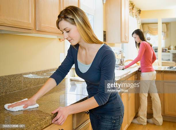 Two teenage sisters (16-18) cleaning kitchen counter