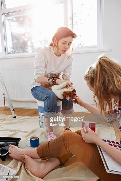 two teenage sisters with color swatches, coffee and a cat - jeune fille rousse photos et images de collection