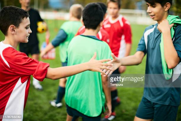 two teenage soccer players greet each other after the match. - sports training camp stock pictures, royalty-free photos & images
