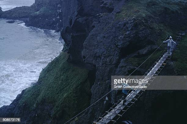 Two teenage travelers crossing a rope bridge over a ravine near fjords along the coast of Scotland on a stormy day Scotland 1966