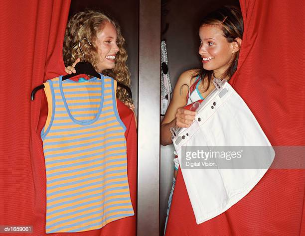 Two Teenage Women Standing in Changing Rooms Comparing Clothes