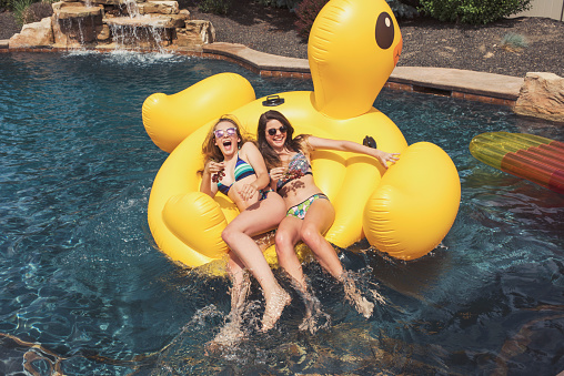 Two teenaged girls on rubber duck raft in swimming pool - gettyimageskorea