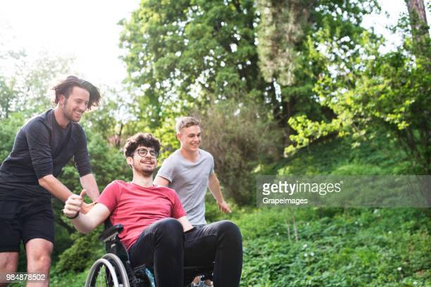 Two teenager boys with a disabled friend in wheelchair running outside in nature.