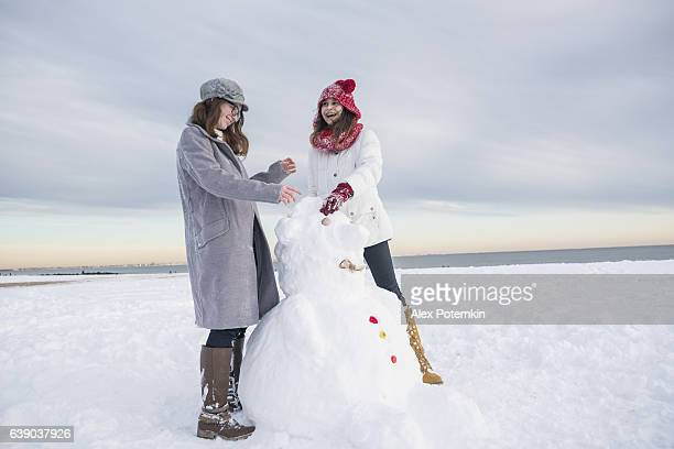Two teenager girls, friends, make the snowman at the beach