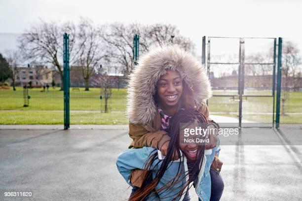 two teenager girls (12-13, 14-15) playing in park - 12 13 jaar stockfoto's en -beelden