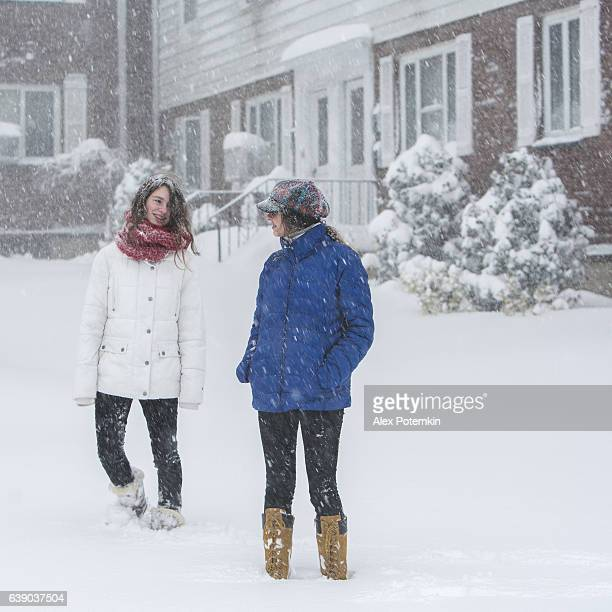 Two teenager girls plays under snowfall at the street