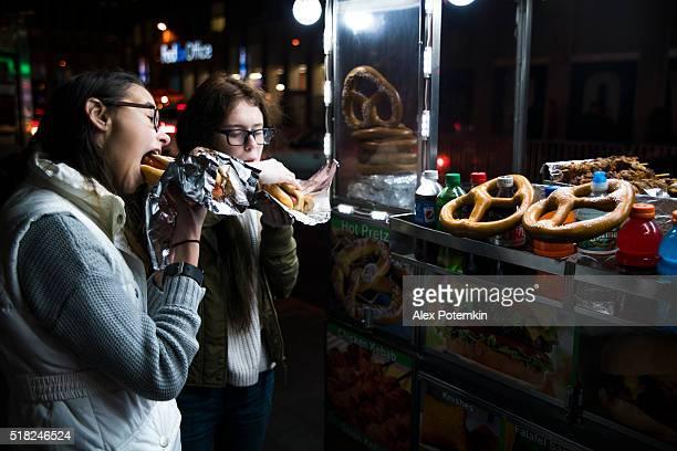 Zwei teenager-Mädchen, Schwestern, extrafrühes, fastfood auf der Straße
