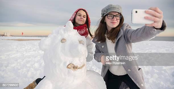 Duas meninas adolescente, irmãs, crie uma selfie com O boneco de neve