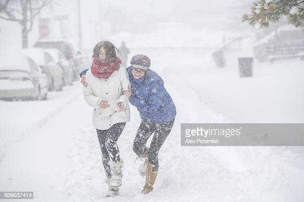 Two teenager girls under snowfall at the street