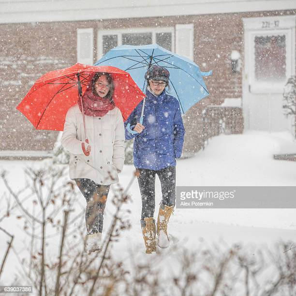 Two teenager girls with umbrellas under snowfall at the street