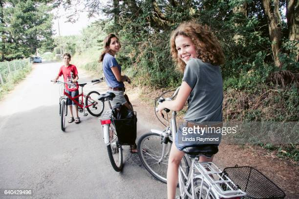 Two teenagers and a boy who ride a bike in a rural road