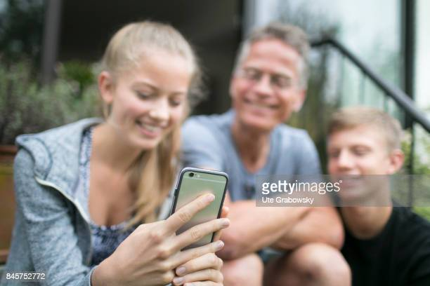Two teenagers and their father are busy with their smartphones Staged picture on August 10 2017 in Duelmen Germany