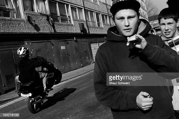 Two teenagers at the Heygate Estate looking directly to the camera as one of them hides a joint in his left hand on March 30 2007 as another teenager...