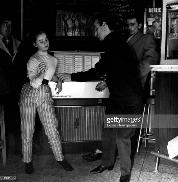 Two teenagers dancing the twist in front of a jukebox with 'vision screen'