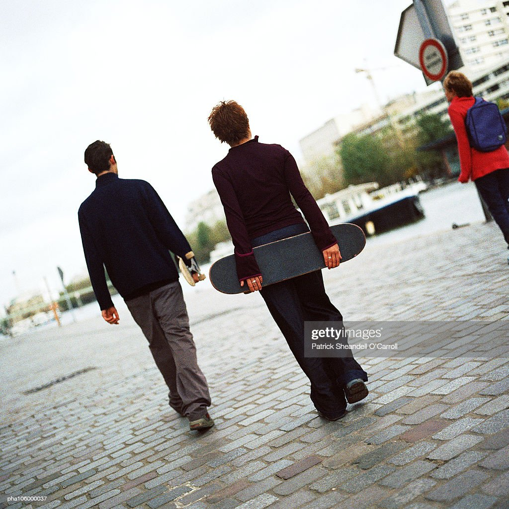 Two teenagers holding skateboards, rear view : Stockfoto