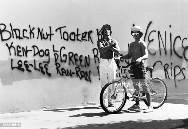 Two teenagers members of the Crips street gang stand in front of a graffiti covered wall in Venice California