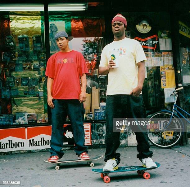 Two teenagers on their skateboards outside some shops USA
